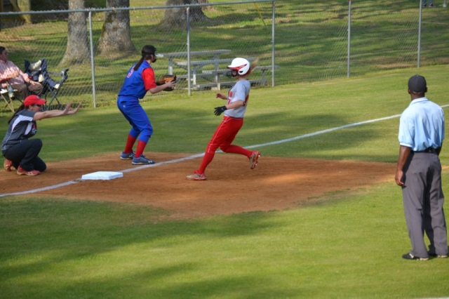 West Union Coach Lisa Bogue hold Callie Baggett at third following her triple that drove in the first two runs of the game on Monday. Photo by Dennis Clayton.