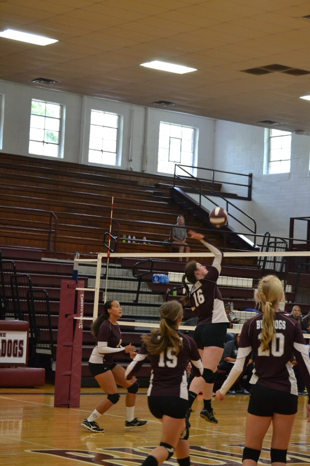 Emma Wilson drives home the spike for New Albany as teammates Meadow Golden, Kaitlyn Cavender and Mary  Day look on. Photo by Dennis Clayton.
