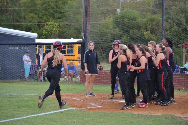 Heather Smith is greeted at home by her teammates following her solo home run against Tupelo. Photo by Dennis Clayton.