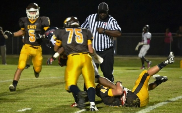 Josh Whitenton hangs on the ball carrier as John Isaac Roberts and Dustin Adams move in to help on the tackle. Photo by Dennis Clayton.