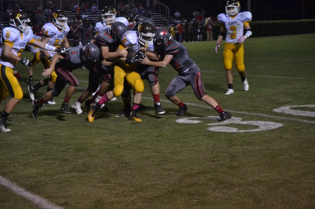 Jamie McCullough is tackled by a host of Walnut players after a short gain. Photo by Dennis Clayton.