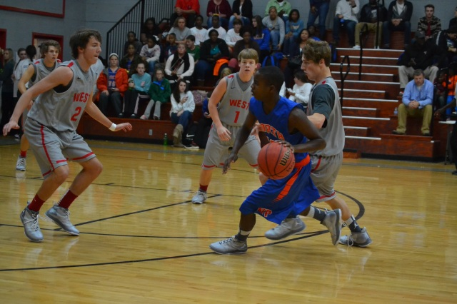 Eli Basil, Hayden Basil and Adam Grubbs surround the North Pontotoc player and the basketball. Photo by Dennis Clayton.