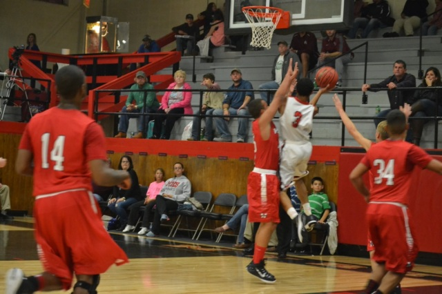 Titus Gillard drives into the lane for the layup over the Wheeler defender. Photo by Dennis Clayton.