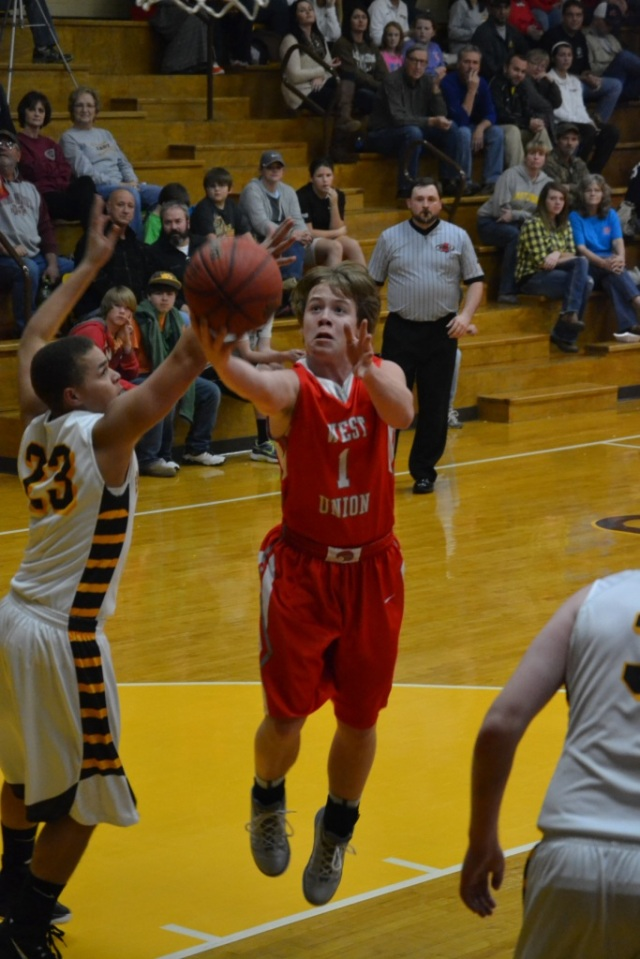 Hayden Basil scored 17 points for West Union on the night. Chase Hall guarding in the lane. Photo by Dennis Clayton.