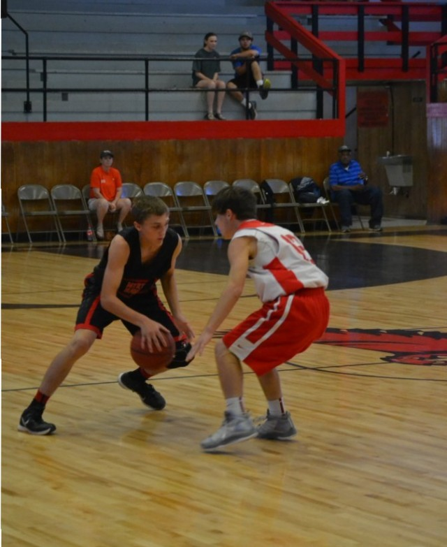 Josh Goolsby going one-on-one against Austin Kiddy with sister Presley Goolsby watching from the stands.